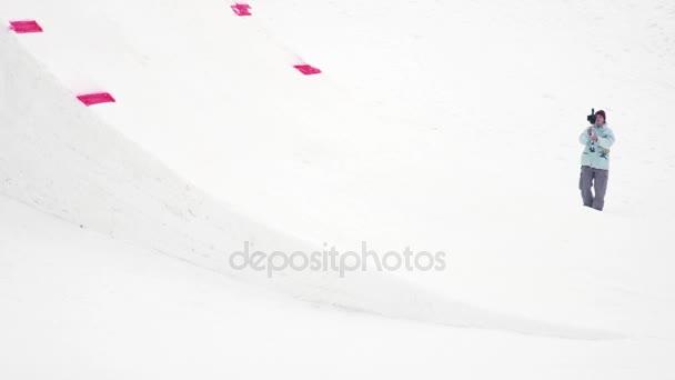Sochi, Rusko - duben 4, 2016: Snowboardista ve žlutém obleku skok z odrazový můstek, aby překlopit ve vzduchu. Hory
