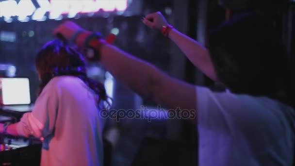 SOCHI, RUSSIA - APRIL 4, 2016: Girl dj spinning at turntable on party in nightclub. Spotlights. Dance. Holidays