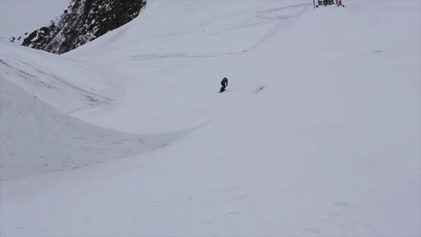 Sochi, Rusko - duben 4, 2016: Snowboardista skok z vysokého můstku na lyžařské středisko. Zasněžené hory. Extrémní