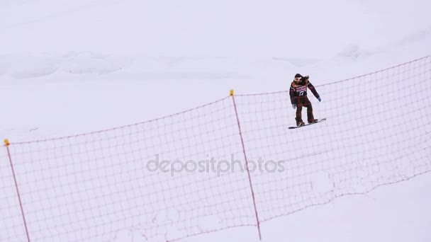 Sochi, Rusko - duben 4, 2016: Snowboardista jízda na svahu, skákat z vysokých odrazový můstek na lyžařské středisko. Krajina