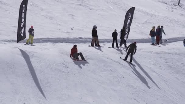 Sochi, Rusko - 1. dubna 2016: Lyžařské středisko. Snowboardista jízda ze svahu. Skokanské můstky. Bílé hory. Lidé
