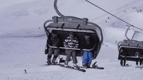 Sochi, Rusko - 1. dubna 2016: Lyžařské středisko. Snowboardisté jezdí na lyžařský vlek. Zasněžená krajina. Slunečno