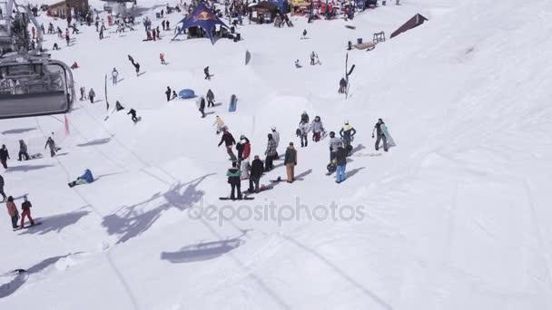 Sochi, Rusko - 1. dubna 2016: Lyžařské středisko. Snowboardisty skočit z můstku. Lyžaři. Encamp. Zasněžené hory