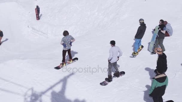Sochi, Rusko - 1. dubna 2016: Lyžařské středisko. Snowboardisty jízda ze svahu. Lyžaři. Extrémní sport. Zasněžené hory