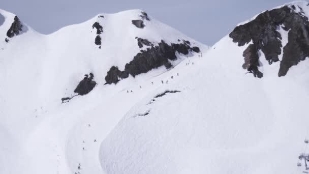 Sochi, Rusko - 1. dubna 2016: Lyžařské středisko. Snowboardisty a lyžaře jezdit na svazích. Encamp. Hory. Slunečný den