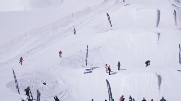 Sochi, Rusko - 1. dubna 2016: Lyžařské středisko. Snowboardisty a lyžaře jezdit na svazích, skok z skokanské můstky