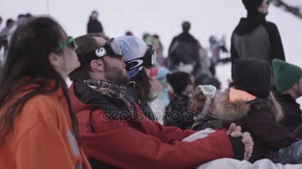 Sochi, Rusko - 1. dubna 2016: Lyžařské středisko. Snowboardisty a lyžaře tleskat v encamp. Muže a dívky. Oblečení