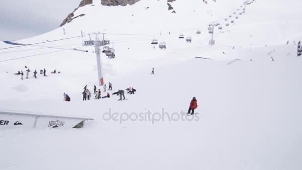 SOCHI, RUSSIA - APRIL 1, 2016: Ski resort. Skier slide on trail, ride on slope. People. Snow mountains. Extreme
