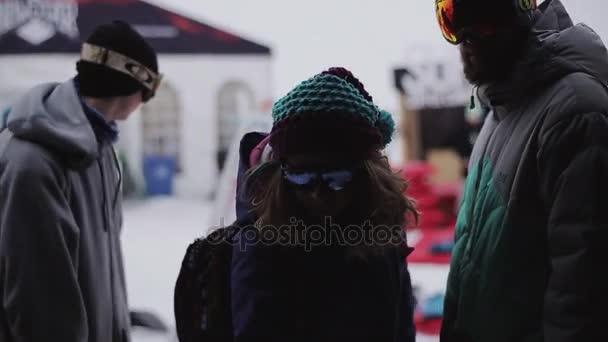 Sochi, Rusko - 6. dubna 2016: Snowboardistů v encamp v lyžařském středisku. Vzít leták. Hory. Lidé. Sluneční brýle