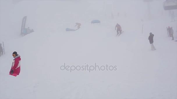 Sochi, Rusko - 6. dubna 2016: Snowboardisty a lyžaře skočit z můstku. Lyžařské středisko. Hora. Lidé. Mlha