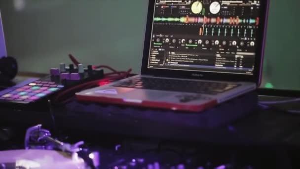SOCHI, RUSSIA - APRIL 8, 2016: Dj spinning at turntable on party in nightclub. Laptop. Purple spotlights.