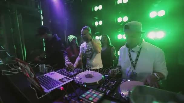 Sochi, Oroszország - április 8-án, 2016: Dj fonó-on fél nightclub lemezjátszó. Az emberek táncoltak. Zöld spotlámpa