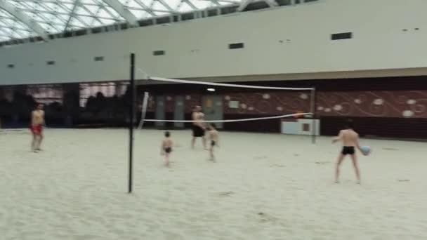 Sochi, Rusko - 8. dubna 2016: Muži hrají volejbal s dětmi na umělé písečné pláži pod střechou budovy