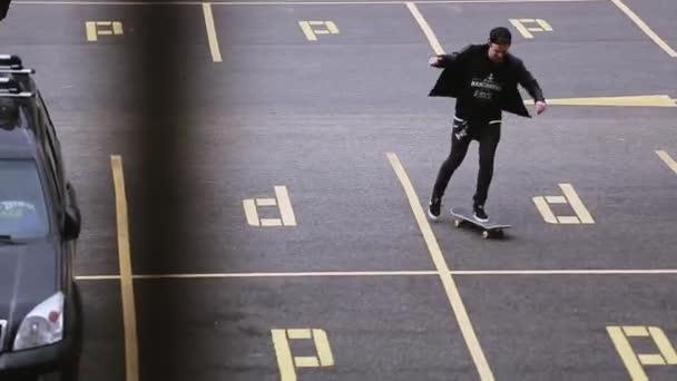 Sochi, Rusko - 8. dubna 2016: Mladý skateboardista v čepici na parkovací místo. Skateboard. Extrémní hobby