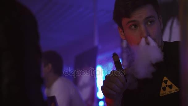 Saint Petersburg, Oroszország - 2016. május 28.: Ember elektronikus cigaretta a dohányzás nightclub. Vapers fesztivál. Az emberek. Steam