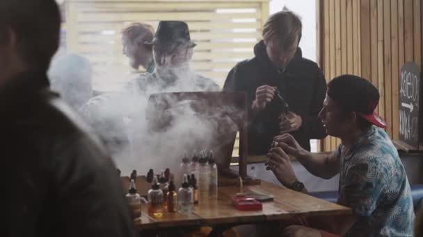 Saint Petersburg, Oroszország - 2016. május 28.: A férfiak füst elektronikus cigaretta speciális boltban, utcán. Vaper fesztivál