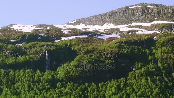 Panoramatický pohled z hory pokryty zelené lesy, sníh na vrcholcích v letní slunečný den. Vodopád. Příroda