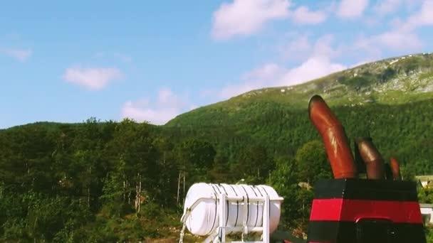 Potrubí na nákladní loď plovoucí řeky na hory porostlé zelené lesy. Přepínač na šířku. Letní slunečný den