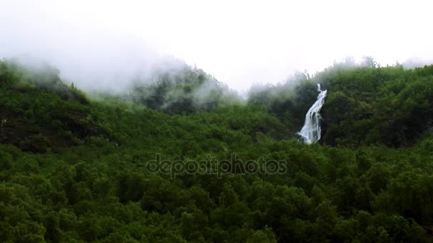 View of cascade waterfall in green woods among mountains. Summer day. Fog. Nature. Nobody. Greenery