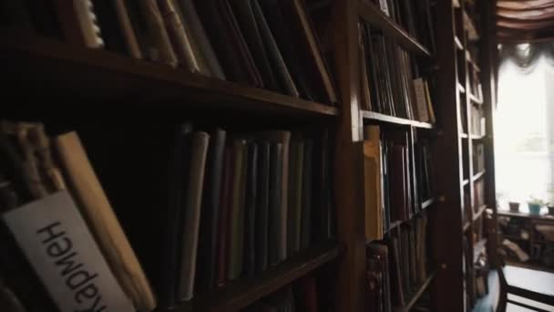 Dolly zastřelil regály ve starém stylu knihovny interiéru. Ruský text, květináče
