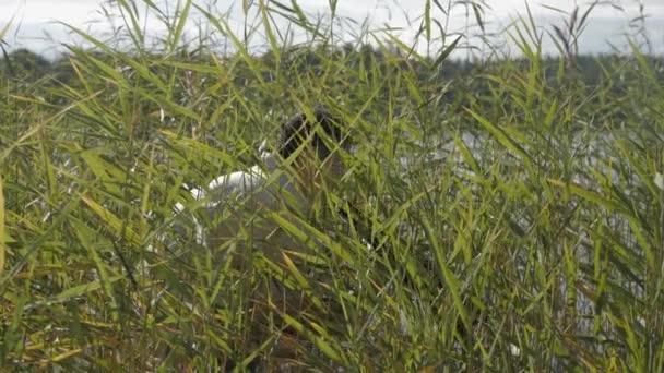 Filmový režisér v síťku vyniknout reed na břehu jezera a křičet do reproduktoru