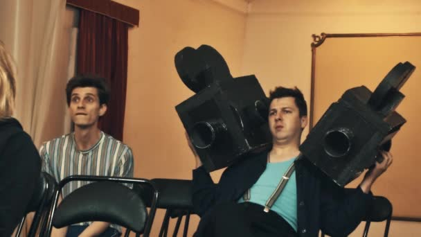 Two guys with huge black fake cardboard camcorders sitting in hall at event