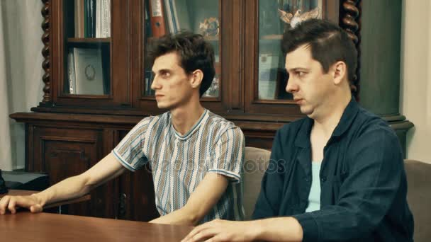 Két munkások kap szidtam főnöke a fa könyvespolc a háttér iroda