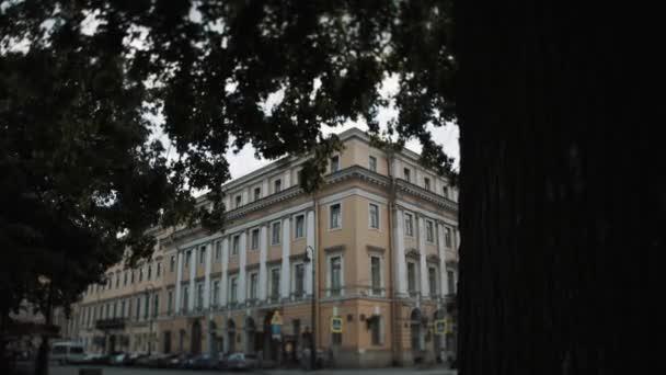 Petrohrad, Rusko - 23. červen 2016: velké stromy před starého stylu koncertní sál budovy na rohu ulice město