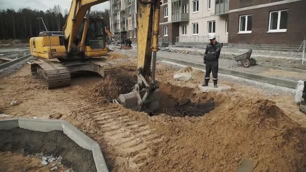 Petrohrad, Rusko - 26 září 2016: Slowmotion žlutý bagr kopání písku v příkopu na staveništi