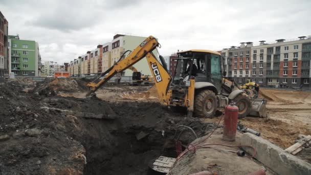 SAINT PETERSBURG, RUSSIA - SEPTEMBER 26, 2016: Slowmotion bulldozer excavator dump soil in to sewer trench at building site