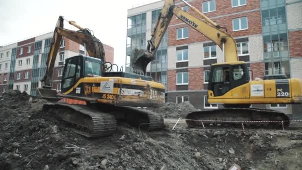 SAINT PETERSBURG, RUSSIA - SEPTEMBER 26, 2016: Slowmotion dolly shot two black and yellow excavators at building site