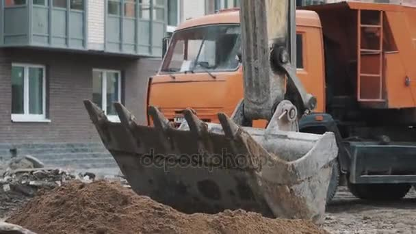 Petrohrad, Rusko - 26 září 2016: Rypadlo lopaty hromadu písku, oranžový vůz prochází na staveništi