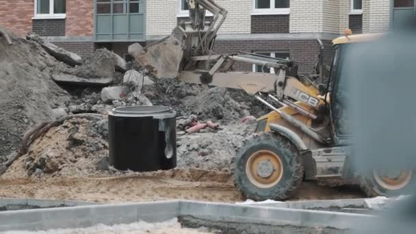 SAINT PETERSBURG, RUSSIA - SEPTEMBER 26, 2016: Bulldozer ride on building site with concrete manhole ring swinging on chains
