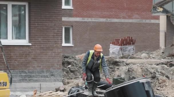 Petrohrad, Rusko - 26 září 2016: Tvůrce v tvrdé klobouku vytáhl prsten betonové šachty na buldozer na staveništi