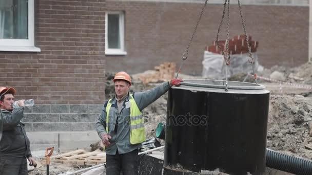 Petrohrad, Rusko - 26 září 2016: Pracovník v tvrdé klobouku vytáhl prsten betonové šachty se buldozer na staveništi