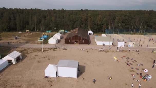 SAINT PETERSBURG, RUSSIA - JULY 30, 2016: Aerial shot sandy beach with white tents and sports ground. Kite flying in sky
