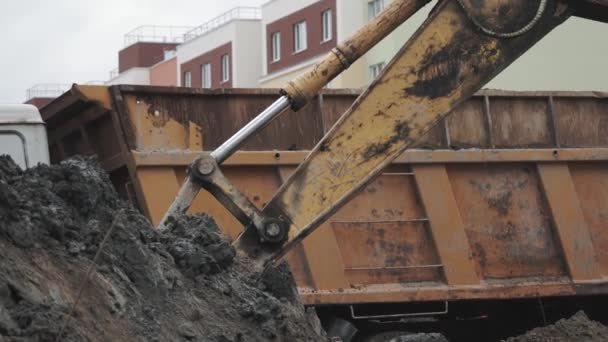 Slowmotion excavator bucket dig soil and dump in back of truck at building site