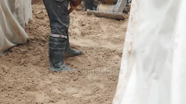 Slowmotion worker in rubber boots with shovel smoothing sand in trench