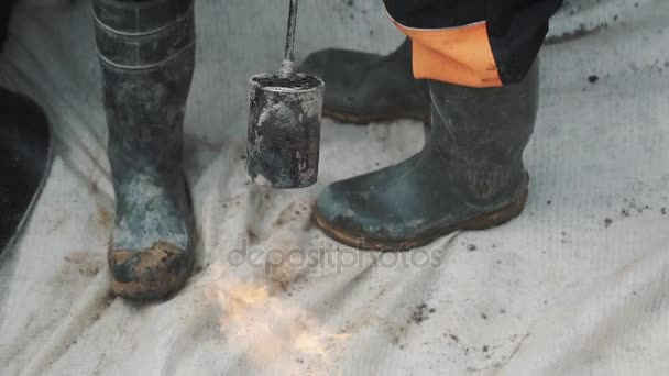 Flaming Gas Torch Burning Whit Cloth Material With Two Pair Of Rubber Boots On Stock