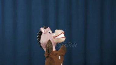 Hračka kůň maňáska provádějte pohyby paže šířit na scénu modré pozadí