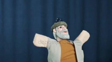 Rolník maňáska se jeví pozdravit publikum, náruč šíří na modrém pozadí