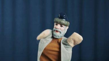 Letitý muž maňáska vytvořit obličej dlaněmi v nouzi na scéně s modrým pozadím