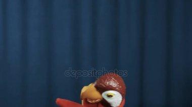 Maňáska papouška běžet na scénu vlny a vyprávět příběh na modrém pozadí