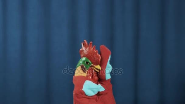 Kohouta maňáska vytvořit obličej dlaněmi v nouzi na scéně s modrým pozadím