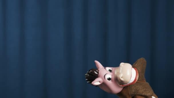 Koně maňáska dělá nezapomenutelný konec na scéně s modrým pozadím