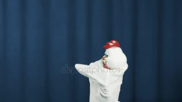 Kuřecí maňáska kývl hlavou tančí na scénu s modrým pozadím