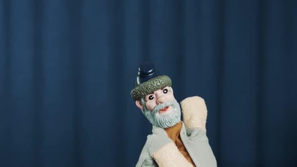 Starý muž maňáska si ještě hlavu, ohřívá se davu na scéně s modrým pozadím