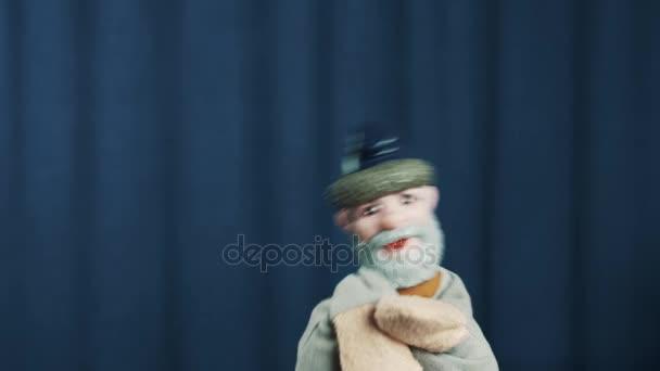Starší muž maňáska opakovaně si ještě hlavu, tanec na scéně modré pozadí