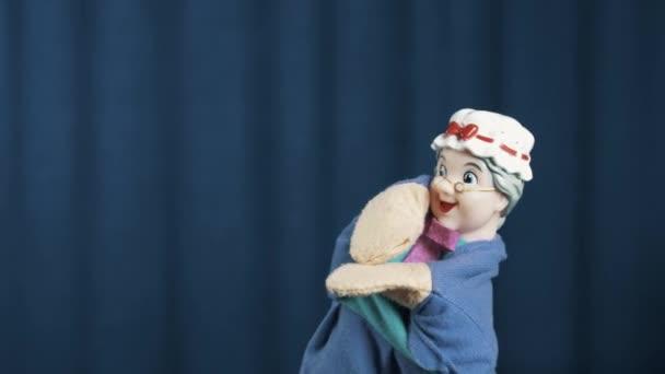 Starší žena maňáska je házet pohyb a tanec na modrém pozadí