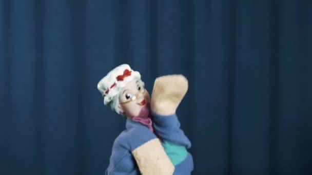 Objeví se na scéně hladké taneční pohyby na modrém pozadí stará žena maňáska